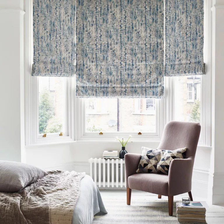 Blue watercolor roman shades over bay window with white painted floor boards and accent armchair
