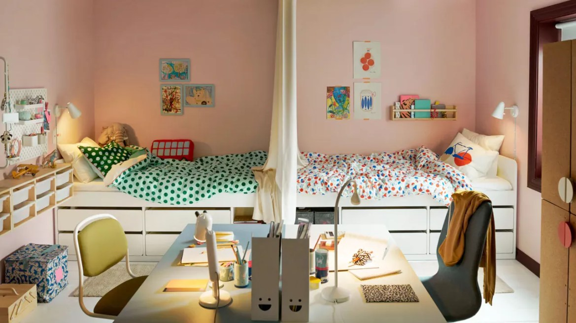 Kids shared bedroom ideas in a pink scheme with symmetrical white beds, drawers and desk areas and colorful bedlinen and accessories.