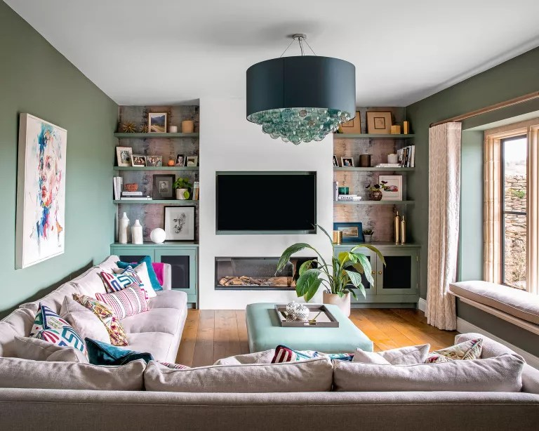 Green living room with l-shaped sofa and wall-mounted tv