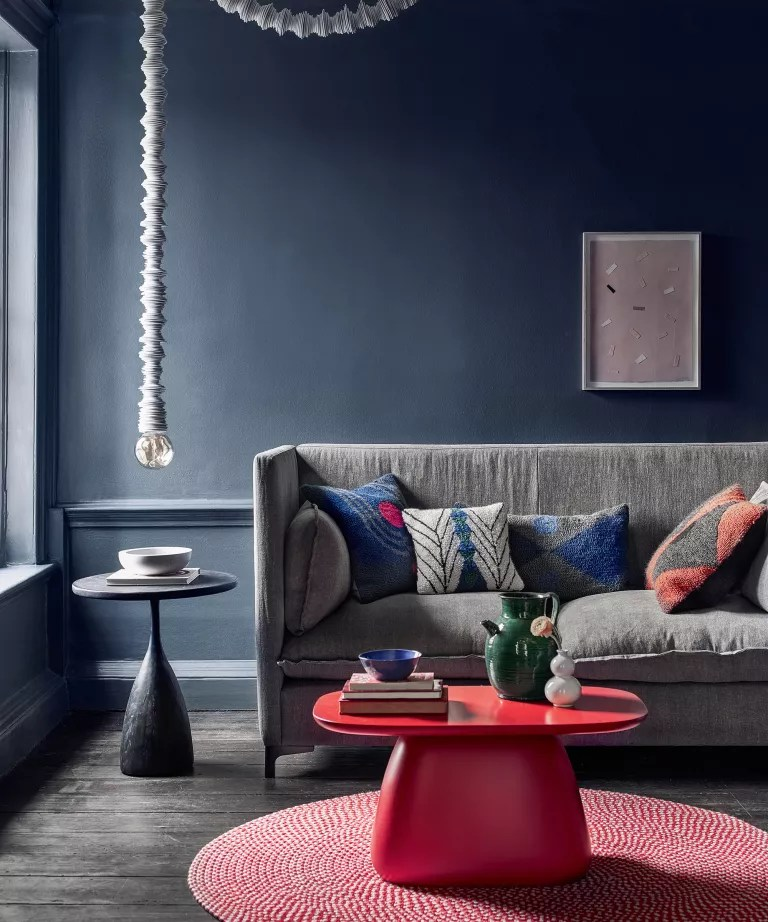 A living room with grey sofa, blue walls and red coffee table