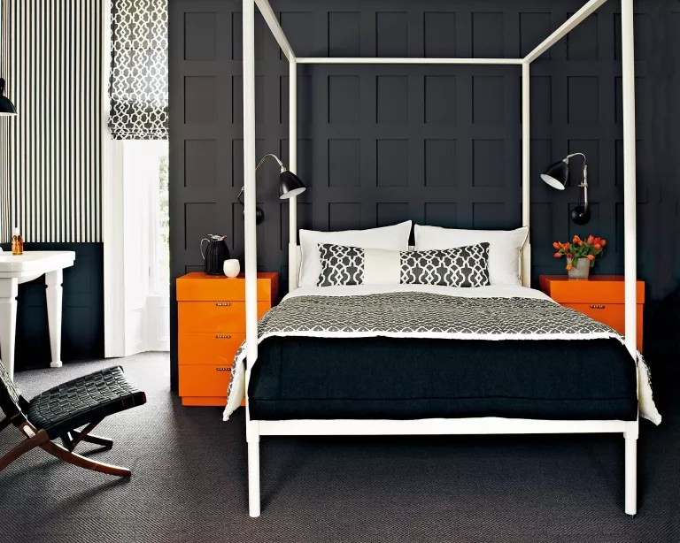 A bedroom with black panelled walls, white four poster bed, black and white soft furnishings and orange side tables