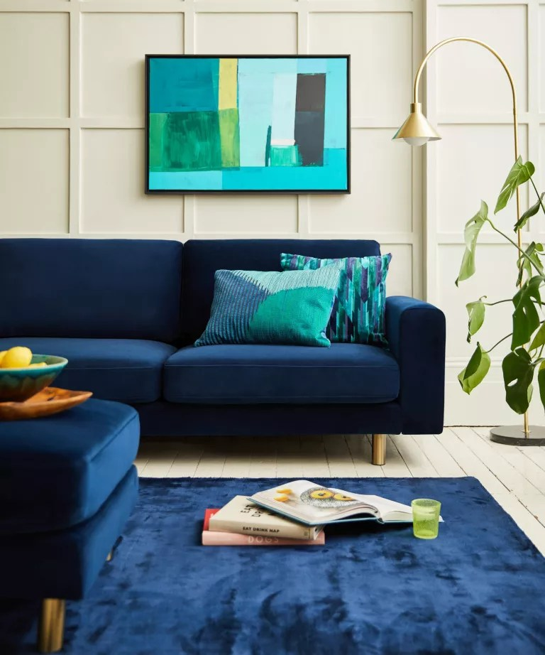 A living room with cream panelled walls and a blue navy velvet sofa
