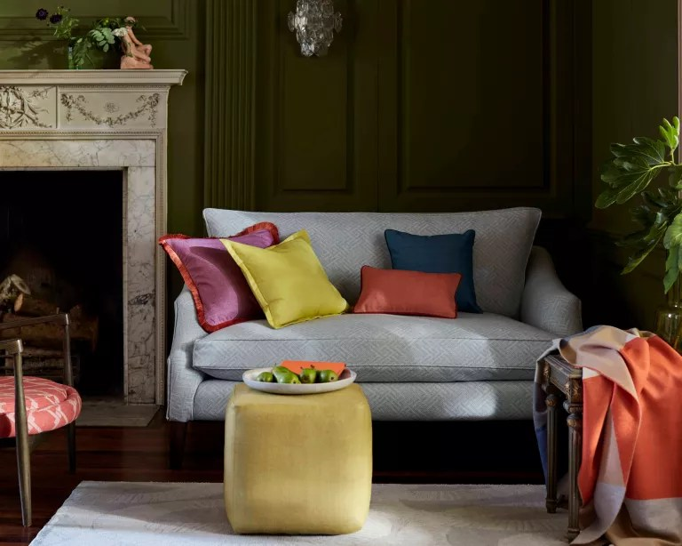 A dark green living room with grey sofa and bright colored cushions