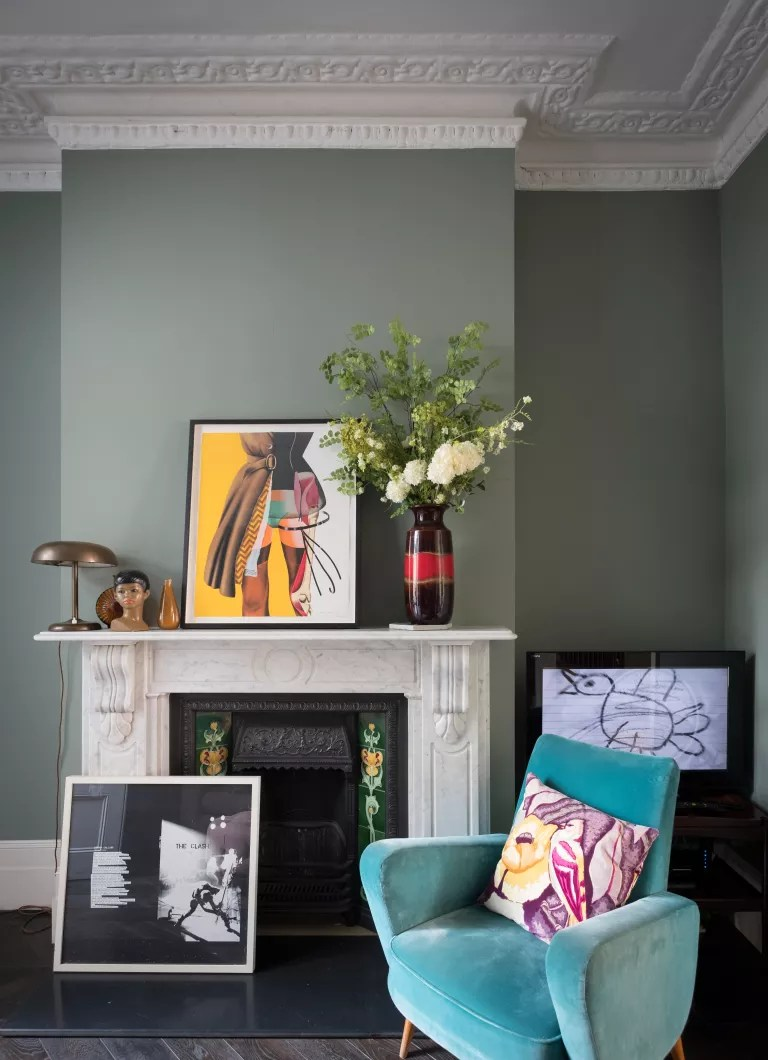Green living room with white fireplace with blue velvet chair