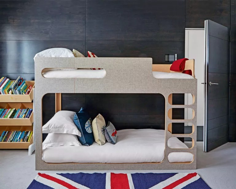 A kids' room with wood-panelled walls, bunk bed and Union Jack rug