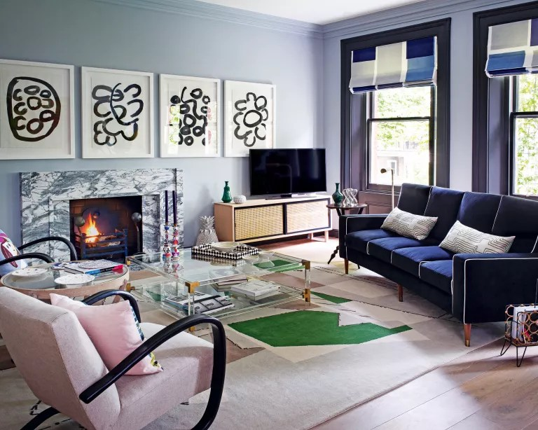 A living room with pale blue walls, a marble fireplace, dark blue sofa and pale pink armchairs
