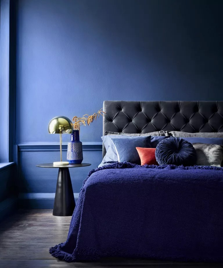 A bedroom with deep blue walls and a bed with blue velvet headboard
