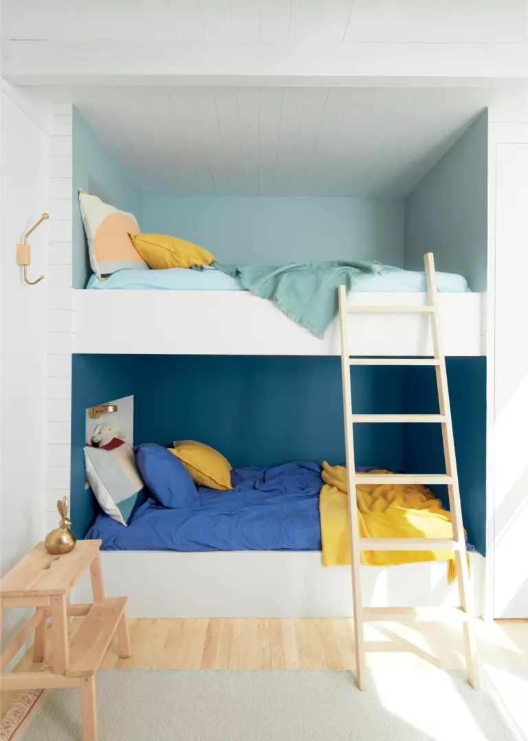 White bunk beds built into the wall with fun matching wall paint for each bed's bedcovers, illustrating clever shared bedroom ideas.