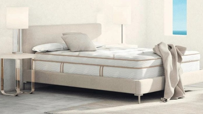 Saatva vs Avocado: The Saatva Latex Hybrid Mattress shown on a beige fabric covered bedframe