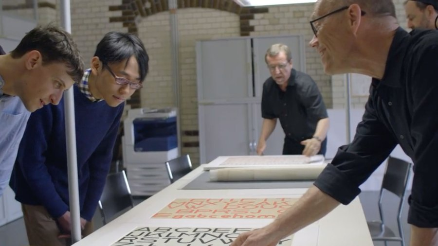 Erik Spikermann and two design students study a sheet of Bauhaus typography
