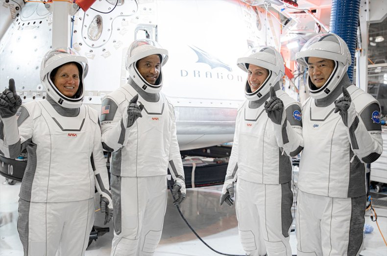 "SpaceX's Crew-1 astronauts, including NASA astronauts Shannon Walker, Victor Glover and Michael Hopkins and JAXA astronaut Soichi Noguchi, pose in front of their Dragon capsule, ""Resilience,"" at SpaceX's headquarters in Hawthorne, California."