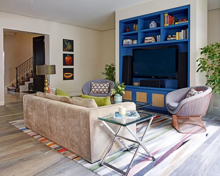 Living room with blue painted TV alcove and storage