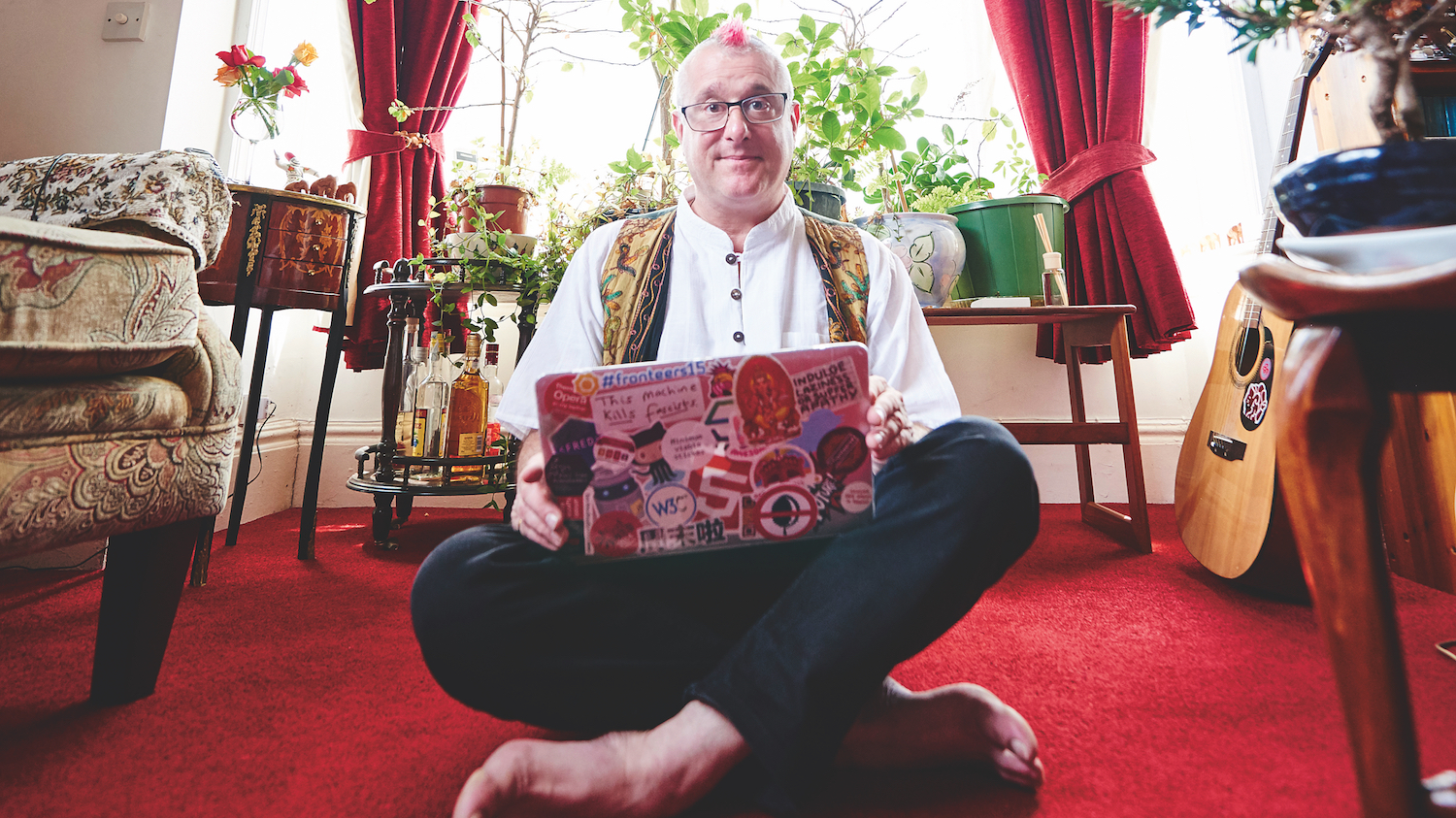 Bruce Lawson sat cross legged on a red carpet in his living room with a laptop.