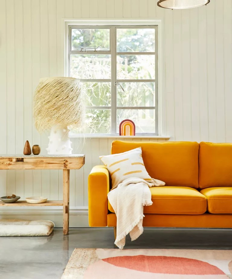 A living room with a turmeric yellow sofa from Snug