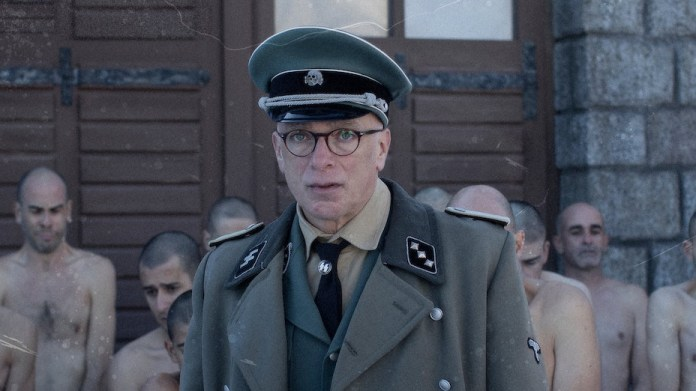 A soldier and prisoners in a Nazi concentration camp in The Photographer of Mauthausen, one of the best Netflix war movies