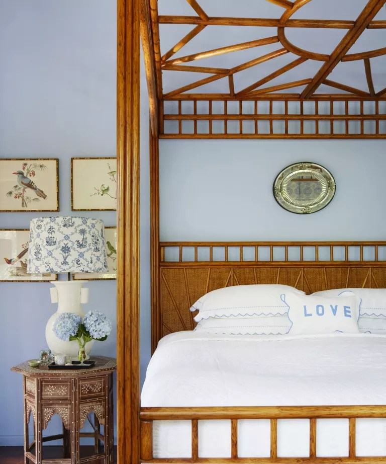 A bedroom with periwinkle blue walls and rich brown four poster bed