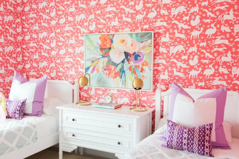 Bright pink animal wallpaper and simple, elegant white painted furniture, with floral wall art and purple and white bedlinen.
