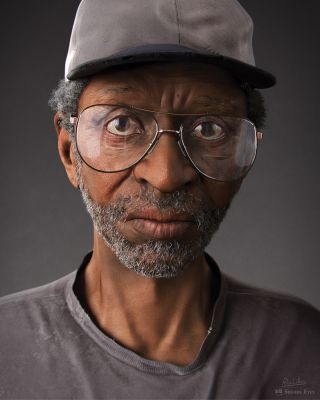 Portrait of a man wearing glasses and a cap
