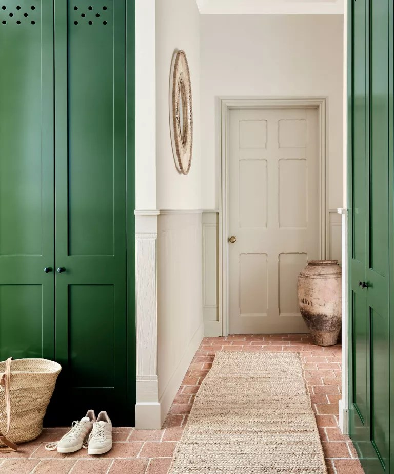 Hallway with green paintwork on cabinets and sisal runner towards door