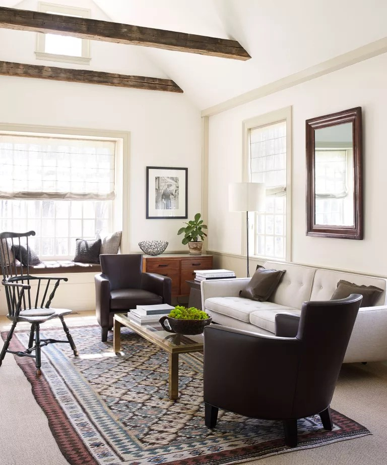 Simple cream living room with wood furniture, leather armchairs and rug