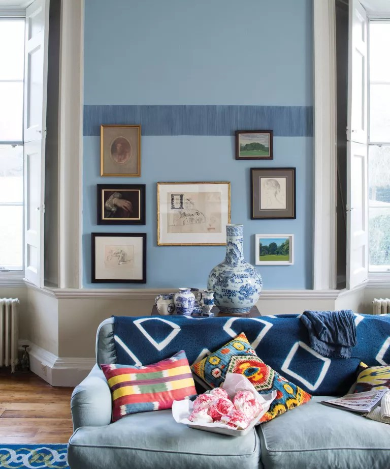 A living room with pale blue walls and a darker textured border, with white woodwork and a blue tie dyed sofa
