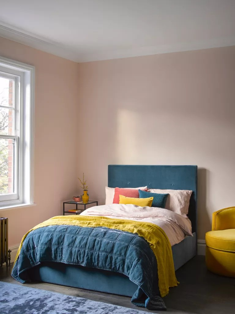 pink bedroom with teal bed and accents of yellow
