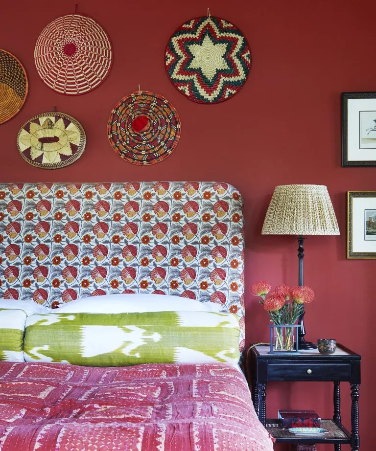 An example of bohemian bedroom ideas showing a bedroom with a red wall and a floral headboard with ikat prints and basketwork plates