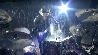 Metallica's Lars Ulrich plays in the pouring rain in Manchester