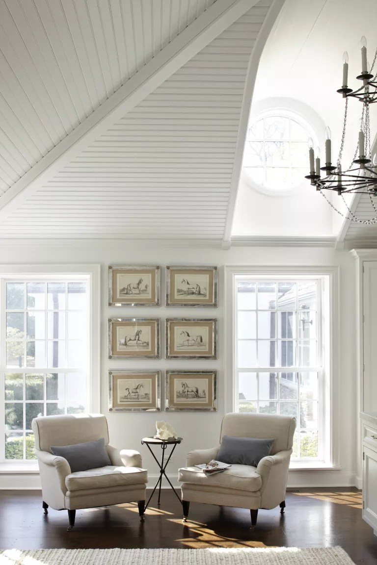 white living room with two armchairs and shiplap ceiling painted white