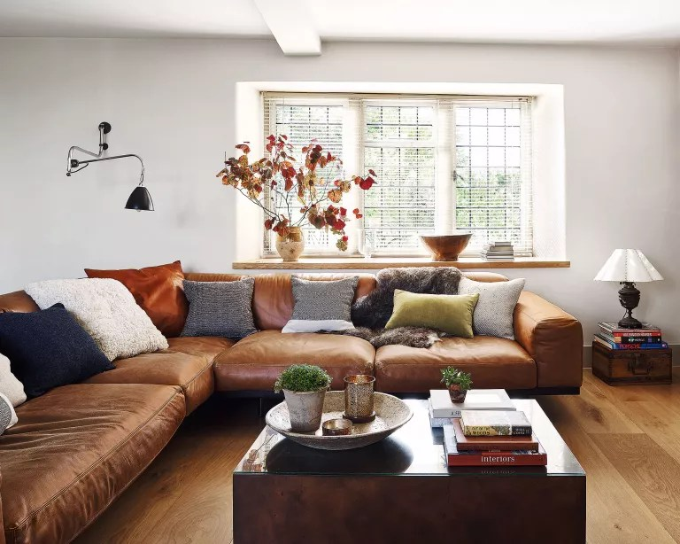 Scandinavian living room with wood floor, leather sofa and white painted walls