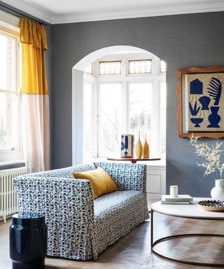 A living room curtain idea with blue patterned wallpaper and yellow and white color-blocked curtain