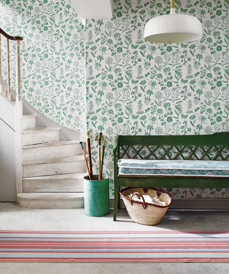 Hallway with green floral wallpaper and green bench