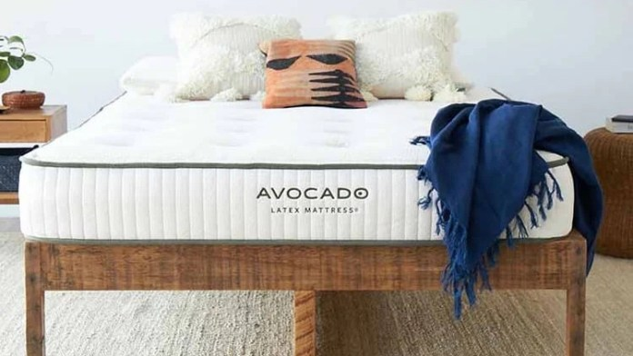 Saatva vs Avocado: The Avocado Latex Mattress on a dark wooden bed frame and dressed with a navy throw