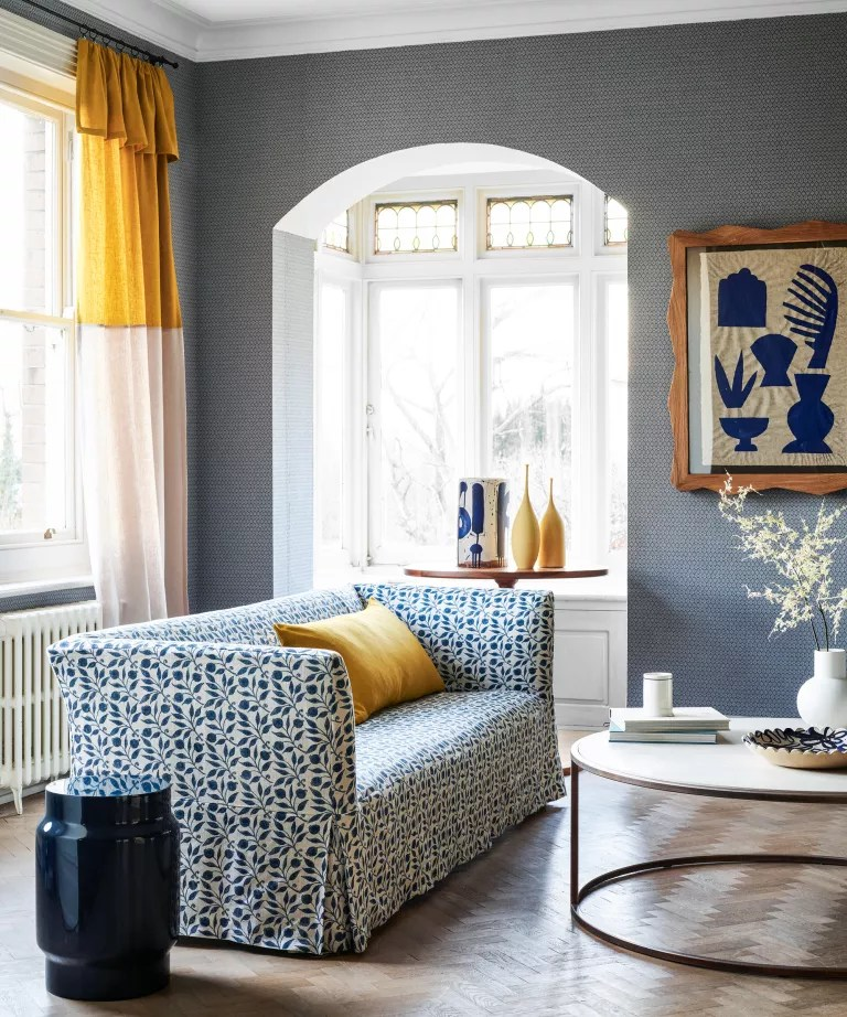 A living room with blue wallpaper and yellow accents