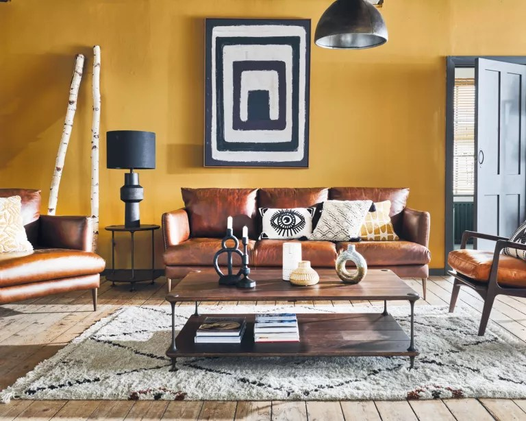 Living room fall decor with yellow wall and leather sofa