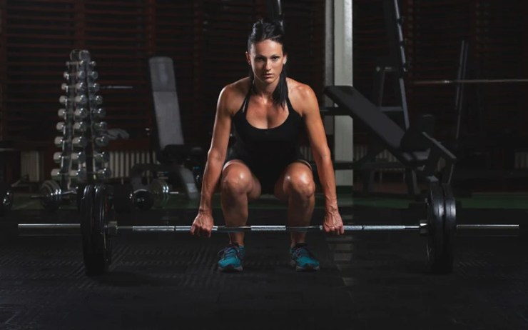 woman deadlifts at the gym