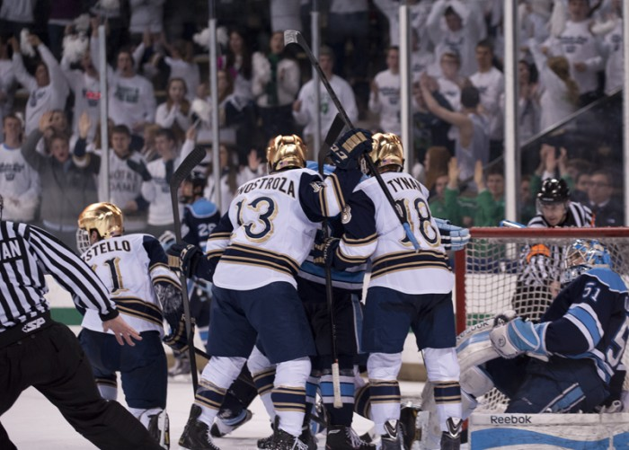 Freshman center Vince Hinostroza, center, and senior center T.J. Tynan jostle with Maine players during Maine's 2-1 win over the Irish on Feb. 7.  A tying goal scored by senior left wing Jeff Costello was called off by the officials.