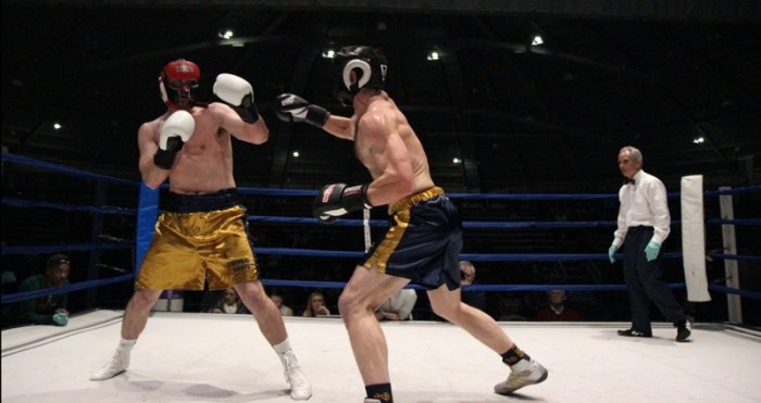 Captain and law student Brian Ellixson, right, lands a jab despite the best efforts of junior Ryan Lindquist to get out of the way.  Ellixson and Lindquist clashed in the semifinal round Tuesday night in the Joyce Center Fieldhouse. Ellixson took the victory by unanimous decision and advanced to the finals Sunday.