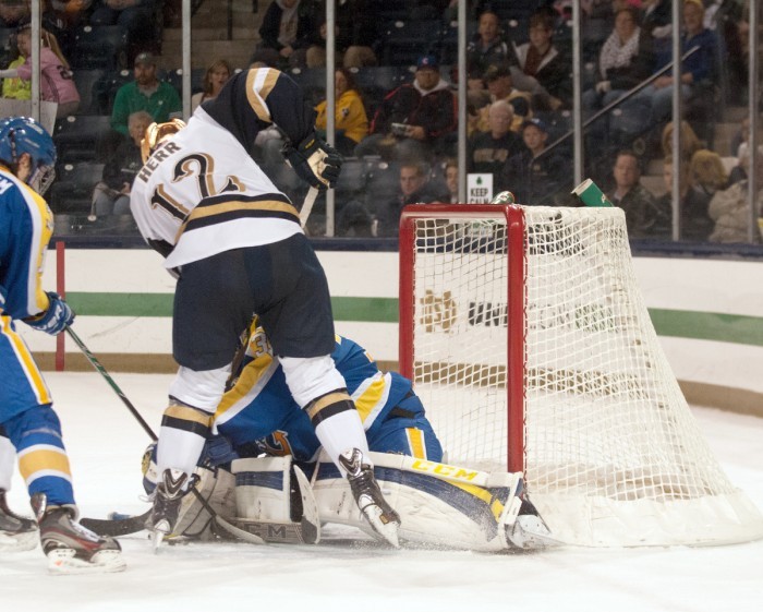 Irish junior left wing Sam Herr crashes the net against Lake Superior State on Oct. 17, at Compton Family Ice Arena. Herr has three goals on the season while junior left wing Mario Lucia leads the team with six.