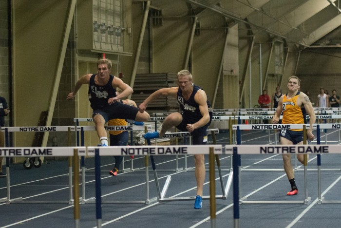 Irish junior Brent Swanberg, center, storms through the 60-meter hurdles during the Blue and Gold Invitational on Dec. 5.