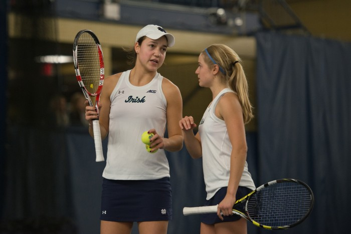 Notre Dame's top doubles duo of junior Quinn Gleason, left, and sophomore Monica Robinson talk strategy during Notre Dame's 6-1 loss to Stanford on Friday at Eck Tennis Center.