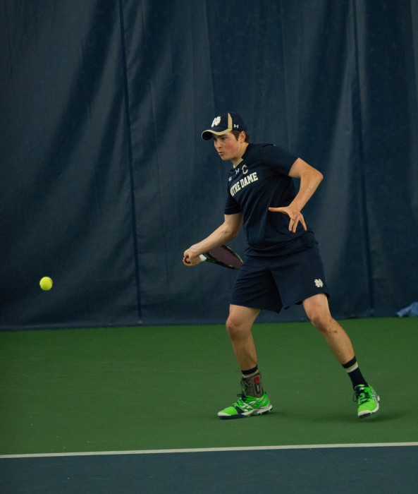 Irish junior captain Eric Schnurrenberger swings at the ball during his Jan. 24 match against Oklahoma State at Eck Tennis Pavilion.