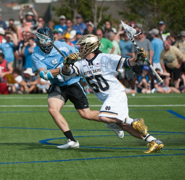 Junior attack Matt Kavanaugh protects the ball from a North  Carolina defender. Kavanaugh had four goals in the Irish win.