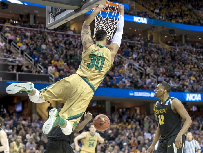 Irish junior forward Zach Auguste swings on the rim after dunking for two of his 15 points during Notre Dame's 81-70 win over Wichita State in their Sweet 16 game. Auguste also pulled down six rebounds.