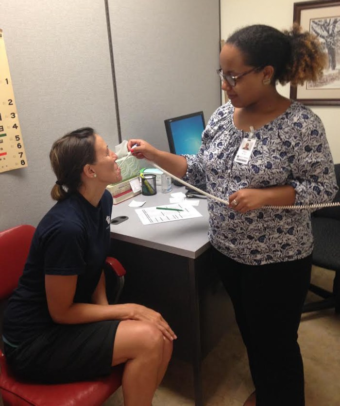 Senior Alexandra Rice treats a patient at the Roanoke Rescue Mission's G. Wayne Fralin Free Clinic for the Homeless.