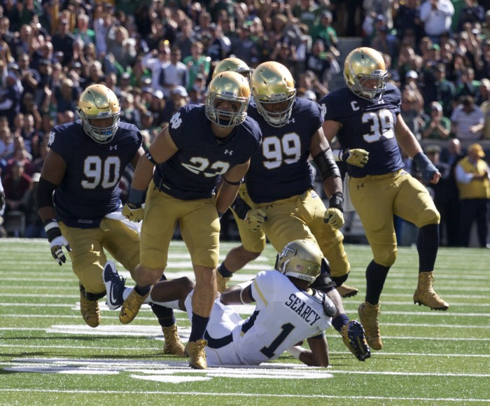 Flanked by his teammates, sophomore safety Drue Tranquill celebrates a third-down stop Saturday.