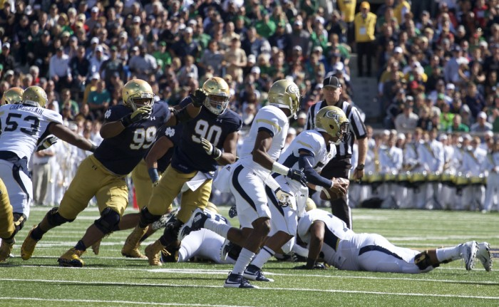 Freshman defensive lineman Jerry Tillery, left, and junior defensive lineman Isaac Rochell pursue Georgia Tech redshirt junior quarterback Justin Thomas during Notre Dame's 30-22 win Saturday at Notre Dame Stadium.