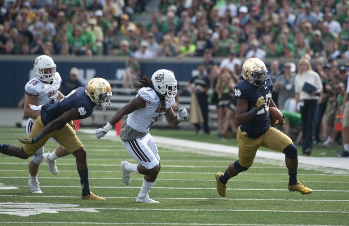 Irish senior running back C.J. Prosise turns the corner during his first-quarter, 57-yard touchdown run that opened the scoring in Notre Dame's 62-27 win over Massachusetts on Saturday at Notre Dame Stadium. It was the first of two scores on the day for Prosise, who topped 100 rushing yards for the third consecutive game.