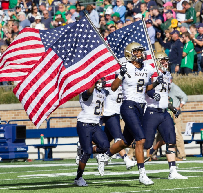 Navy players take the field carrying American flags before the game Saturday at Notre Dame Stadium.