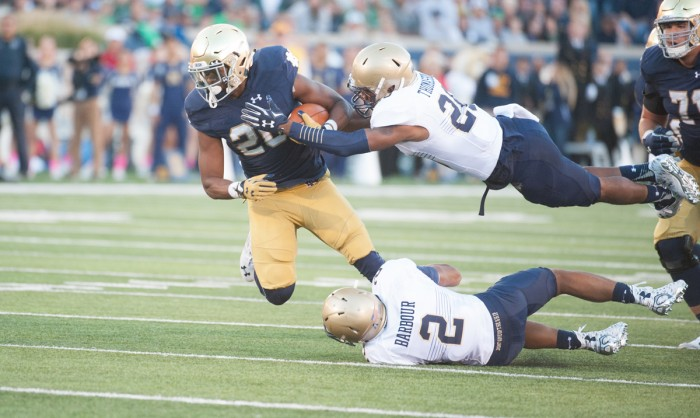 Senior running back C.J. Prosise attempts to evade two defenders during Notre Dame's 41- 24 victory over Navy on Saturday.